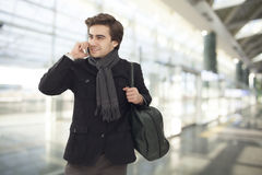 Ung affärsman som talar på mobiltelefonen i flygplats arkivfoton
