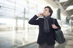 Ung affärsman som talar på mobiltelefonen i flygplats arkivbilder