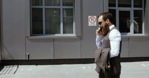 Ung affärsman som talar på mobiltelefonen och går i gatan
