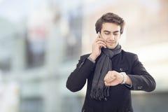 Ung affärsman som talar på mobiltelefonen och ser klockan på gatan Royaltyfria Foton