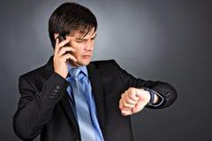 Ung affärsman som talar på telefonen, medan se hans klocka Arkivfoton