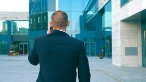 Ung affärsman som talar på telefonen och går i gata Oigenkännlig man som har affärskonversation under lager videofilmer