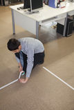 Ung affärsman som tejpar upp golvet i kontoret Arkivfoto