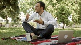 Ung affärsman som tycker om mat som han kom med i en lunchask hemifrån Lunchtime på parkera utomhus royaltyfria bilder