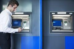 Ung affärsman som ut tar pengar från ATMEN och ner ser på hans telefon Royaltyfria Foton