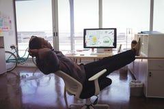Ung affärsman som vilar på stol i idérikt kontor Royaltyfri Bild