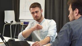 Ung affärsman som visar hans mogna kollega något på bärbara datorn arkivfilmer