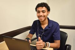 Ung affärsman Working On Laptop med tummar upp arkivbild