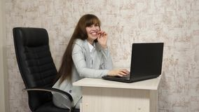 ung aff?rskvinna i hennes arbetsplats H?rlig aff?rskvinnakvinna i aff?rs?verensst?mmelse p? en b?rbar dator f?rv?nadt barn f?r r? lager videofilmer