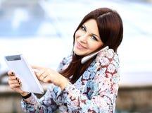 Ung affärskvinna som använder den digitala minnestavlan och mobiltelefonen Arkivfoto