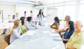 Ung affärskvinna som i regeringsställning framlägger Arkivfoton