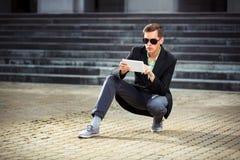 Ung affärsman som använder en utomhus- minnestavladator Arkivbild