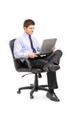 Ung affärsman som i regeringsställning sitter stolen Arkivfoton