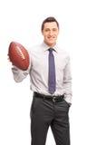 Ung affärsman som rymmer en amerikansk fotboll Arkivbild