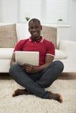 Ung afrikan som använder den Digital minnestavlan arkivfoton