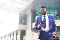 Ung afrikansk affärsman som mycket lämnar kontoret av tillfredsställelse, medan genom att använda hans telefon kopiera avst?nd royaltyfria foton