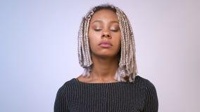 Ung afrikansk allvarlig flicka med dreadlocksflickan som ser kameran, stängande ögon, vit bakgrund lager videofilmer