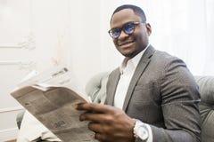 Ung afrikansk amerikanaffärsman i en grå dräkt som läser en tidning, medan sitta på en soffa royaltyfri foto