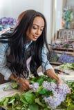 Ung afrikansk amerikanblomsterhandlare som ordnar blommor och ler i blomsterhandel Royaltyfria Bilder