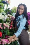 Ung afrikansk amerikanblomsterhandlare som poserar med blommor och ler på kameran Arkivbild