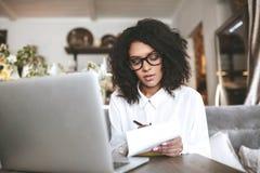 Ung afrikansk amerikanflicka med exponeringsglas som sitter i restaurang och skriver anmärkningar Stående av damen som skriver hä Royaltyfri Fotografi