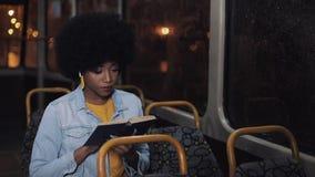 Ung afrikansk amerikankvinna eller passagerareläsebok som offentligt sitter transport, steadicamskott l?ngsam r?relse Stad lager videofilmer