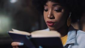 Ung afrikansk amerikankvinna eller passagerareläsebok som offentligt sitter transport, steadicamskott l?ngsam r?relse Stad arkivfilmer