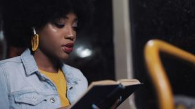 Ung afrikansk amerikankvinna eller passagerareläsebok som offentligt sitter transport, steadicamskott l?ngsam r?relse Stad stock video