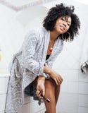 Ung afrikansk amerikankvinna för skönhet i badrock med tandborsten som tar morgonomsorg av henne, livsstilbegrepp arkivbild