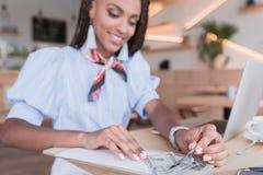 Ung afrikansk amerikankvinna som betalar med kassa arkivbild