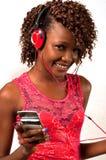 Ung afrikansk amerikankvinna som lyssnar till musik med hörlurar Arkivfoto