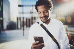 Ung afrikansk amerikanman i headphone som går på den soliga staden och tycker om för att lyssna till musik på hans smarta telefon Royaltyfria Bilder