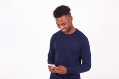 Ung afrikansk amerikanman som överför ett smstextmeddelande på hans sma Royaltyfri Fotografi