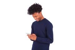 Ung afrikansk amerikanman som överför ett smstextmeddelande på hans sma Royaltyfri Bild