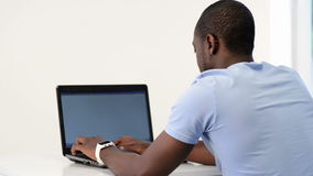 Ung afrikansk amerikanman som använder bärbara datorn lager videofilmer