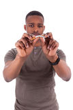Ung afrikansk amerikanman som bryter en cigarett royaltyfri fotografi