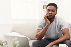 Ung afrikansk amerikanman som har tandvärk hemma royaltyfria bilder