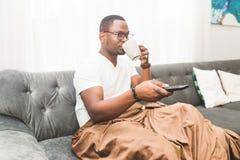 Ung afrikansk amerikanman som hemma täckas med en filt, hållande ögonen på TV royaltyfri foto