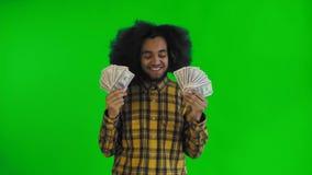 Ung afrikansk amerikanman som rymmer kassapengar på den gröna skärmen eller nyckel- bakgrund för chroma stock video