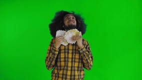 Ung afrikansk amerikanman som rymmer kassapengar p? den gr?na sk?rmen eller nyckel- bakgrund f?r chroma stock video