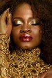 Ung afrikansk amerikanmodell med ljusa röda kanter, guld- makeup och halsbandet som trycker på hennes svarta lockiga hår, stängda Arkivbild