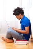 Ung afrikansk amerikanstudent som använder en bärbar dator - afrikanskt folk Arkivfoto