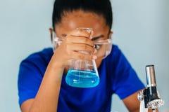 Ung afrikansk amerikanunge som g?r kemiexperiment arkivfoton