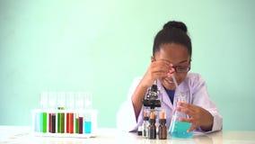 Ung afrikansk amerikanunge som g?r kemiexperiment lager videofilmer