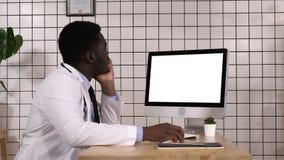 Ung afrikansk doktor som ser på bildskärm av hans dator Vit skärm arkivfilmer