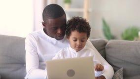 Ung afrikansk farsa som undervisar den lilla fokuserade bärbara datorn för ungesonbruk lager videofilmer