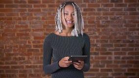 Ung afrikansk flicka med dreadlocks genom att använda en minnestavladator som ser kameran och ler, tegelstenvägg i lager videofilmer