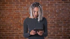 Ung afrikansk flicka med dreadlocks genom att använda en minnestavladator som skriver Tegelstenvägg i bakgrunden stock video