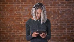 Ung afrikansk flicka med dreadlocks genom att använda en minnestavladator som skriver Tegelstenvägg i bakgrunden lager videofilmer