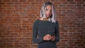Ung afrikansk flicka med dreadlocks genom att använda en smartphone som ser kameran och ler, tegelstenvägg i bakgrunden stock video